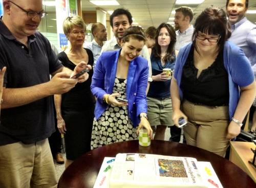 Kristin McKnight and other staff members of The International New York Times bring in the paper's new name with some celebratory cake.